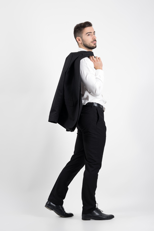 up view: Young elegant luxurious man walking carrying tuxedo over his shoulder looking away. Full body length portrait over gray studio background.