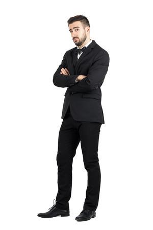 cuerpo hombre: hombre defensiva escépticos con los brazos cruzados mirando a la cámara con recelo. la longitud del cuerpo Retrato completo aislado sobre fondo blanco del estudio. Foto de archivo