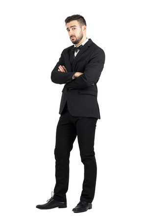 skeptical: Skeptical defensive man with crossed arms looking at camera suspiciously. Full body length portrait isolated over white studio background. Stock Photo