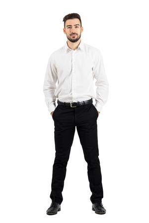 カメラ目線のポケットの手で自信を持ってエレガントなビジネスマン フルボディの長さの肖像画は、白いスタジオ背景に分離されました。