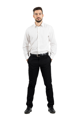 Confident elegant business man with hands in pockets looking at camera.  Full body length portrait isolated over white studio background.