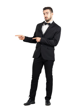 Confused luxurious man with bow tie pointing at copyspace. Full body length portrait isolated over white studio background.