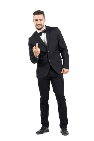 finger bow: Rude young man in tuxedo with bow tie showing middle finger gesture at camera.  Full body length portrait isolated over white studio background.