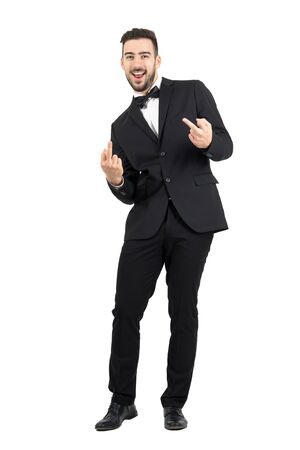 white suit: Young laughing provocative man in suit showing middle finger gesture looking at camera.  Full body length portrait isolated over white studio background. Stock Photo