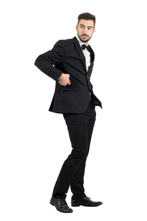 Side view of confident handsome man in tuxedo putting cellphone in coat pocket turning behind.  Full body length portrait isolated over white studio background.