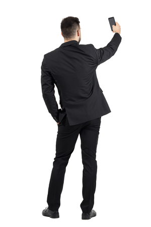 Rear view of young executive in black suit taking photo with his cellphone.  Full body length portrait isolated over white studio background. Standard-Bild
