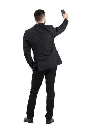 Zadní pohled na mladé výkonné v černém obleku při fotografii s jeho mobil. Celotělový délce portrét na bílém pozadí studio.