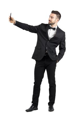 terno: Hombre joven en juego con la pajarita tomando autofoto con el teléfono celular. la longitud del cuerpo Retrato completo aislado sobre fondo blanco del estudio. Foto de archivo