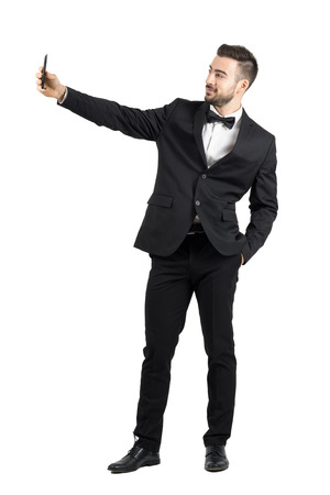 Young man in suit with bow tie taking selfie with cellphone. Full body length portrait isolated over white studio background. Standard-Bild