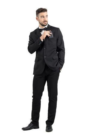 joyful businessman: Relaxed cool handsome man in tuxedo with bow tie putting mobile phone in pocket looking away.  Full body length portrait isolated over white studio background.