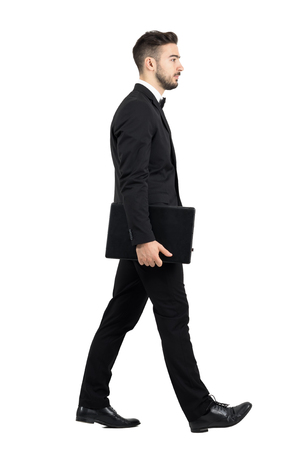 Side view of young executive carrying laptop walking. Full body length portrait isolated over white studio background.