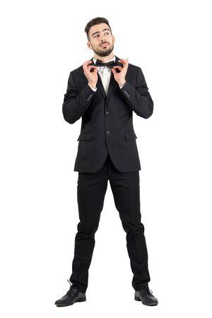 formal dressing: Young stubble groom adjusting bow tie looking up. Full body length portrait isolated over white studio background. Stock Photo