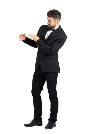 body expression: Young groom with funny expression putting wedding ring on his own finger. Full body length portrait isolated over white studio background.