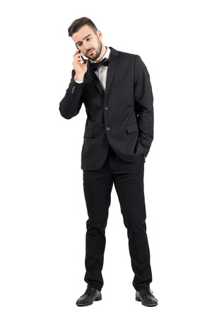 man looking down: Sad young man in suit talking on the phone looking down. Full body length portrait isolated over white studio background.
