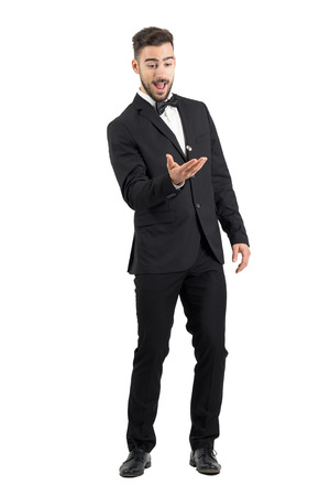 mouth smile: Playful excited young groom tossing wedding ring. Full body length portrait isolated over white studio background. Stock Photo