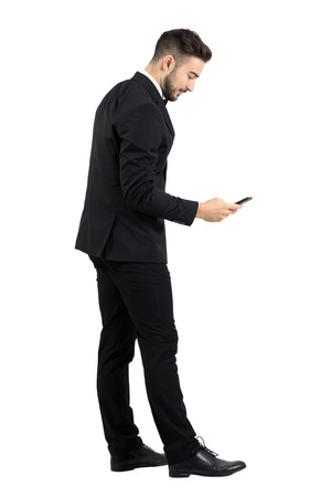 standing businessman: Side view of young businessman in suit typing message on smartphone touchscreen. Full body length portrait isolated over white studio background.