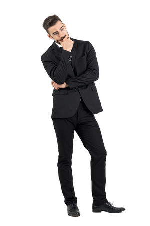 gentleman: Pensive young businessman thinking with hand over his mouth looking away. Full body length portrait isolated over white studio background.