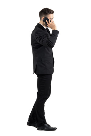 Young businessman talking on the cell phone walking side view. Full body length portrait isolated over white studio background.
