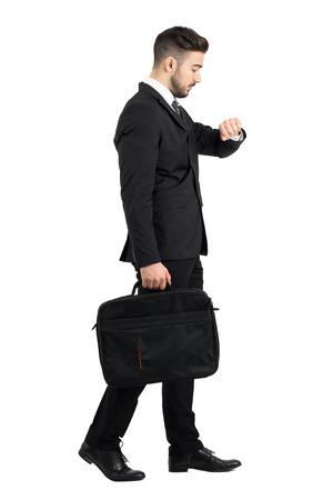 Side view of walking businessman checking hand watch time. Full body length portrait isolated over white studio background.