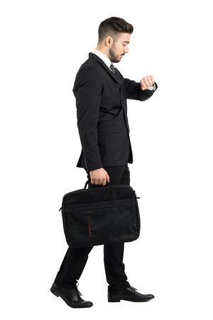 Vista lateral de caminar empresario controlando el tiempo de reloj de la mano. la longitud del cuerpo Retrato completo aislado sobre fondo blanco del estudio. Foto de archivo - 50337837