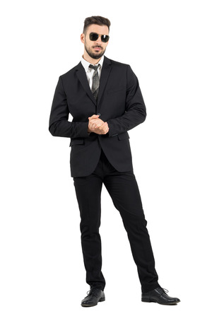 Businessman with sunglasses holding clasped hands. Full body length portrait isolated over white studio background.