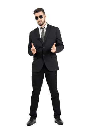 standing businessman: Secret agent with sunglasses aiming hand gun gesture at camera. Full body length portrait isolated over white studio background. Stock Photo