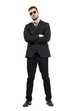 Secret agent or bodyguard with crossed arms looking at camera. Full body length portrait isolated over white studio background. Stockfoto