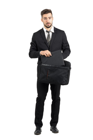 body bag: Serious salesman taking document file out of briefcase looking at camera. Full body length portrait isolated over white studio background. Stock Photo