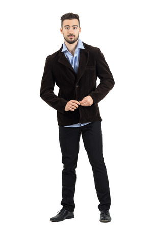 corduroy: Cool relaxed man buttoning corduroy jacket looking at camera. Full body length portrait isolated over white studio background. Stock Photo