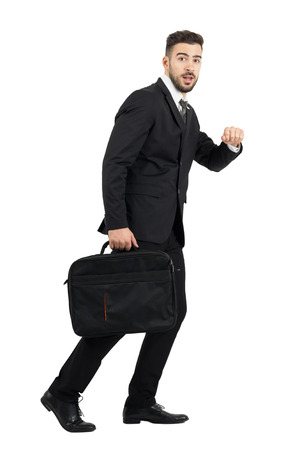 man side view: Running surprised business man carrying laptop case side view looking at camera. Full body length portrait isolated over white studio background.