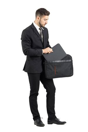 suit case: Salesman taking document folder out of briefcase. Full body length portrait isolated over white studio background.