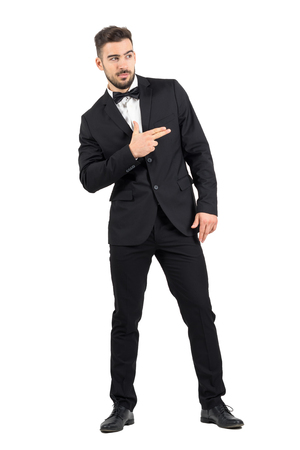 white suit: Funny secret agent with finger gun hand gesture looking away. Full body length portrait isolated over white studio background. Stock Photo
