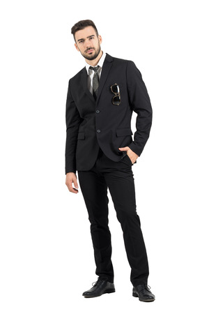rigid: Strict rigid businessman looking at camera with sunglasses in suit pocket. Full body length portrait isolated over white studio background.