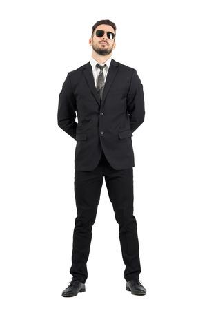 Geheimagent oder Wache mit den Händen hinter dem Rücken tragen sunglasses.Full Körperlänge Porträt isoliert über weiß Studio Hintergrund.