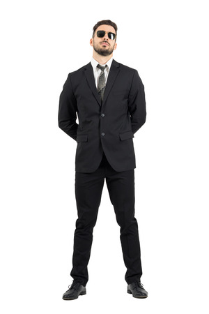 Secret agent or guard with hands behind back wearing sunglasses.Full body length portrait isolated over white studio background.