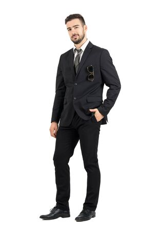 traje: Hombre de negocios confidente en traje con gafas de sol en el bolsillo mirando a la c�mara. Cuerpo completo retrato de cuerpo entero aisladas sobre fondo blanco de estudio.