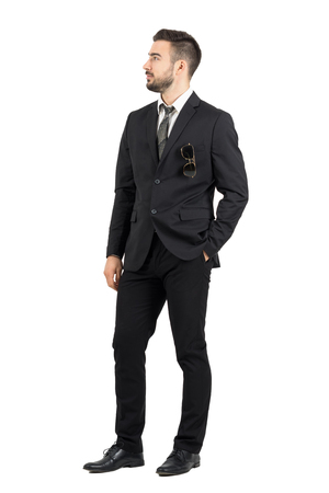 Stylish business man looking away with hand in pocket. Full body length portrait isolated over white studio background.