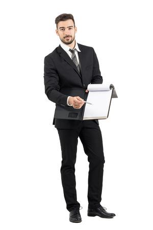 cuerpo hombre: Vendedor joven en traje apuntando espacio de la firma con un contrato de oferta lápiz. Cuerpo completo retrato de cuerpo entero aisladas sobre fondo blanco de estudio.