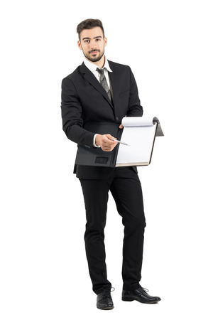 presenting: Young salesman in suit pointing signature space with pencil offering contract. Full body length portrait isolated over white studio background.