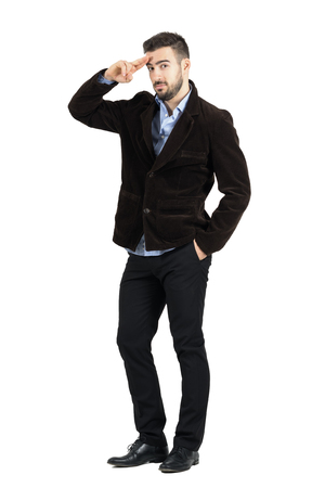corduroy: Young bearded man in corduroy coat saluting at camera. Full body length portrait isolated over white studio background. Stock Photo