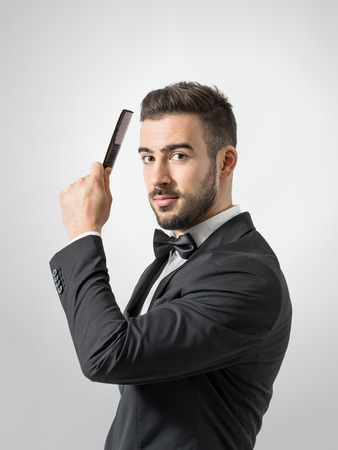 preparation: Side profile view of young man combing hair looking at camera. Desaturated portrait over gray studio background with retro vignette. Stock Photo