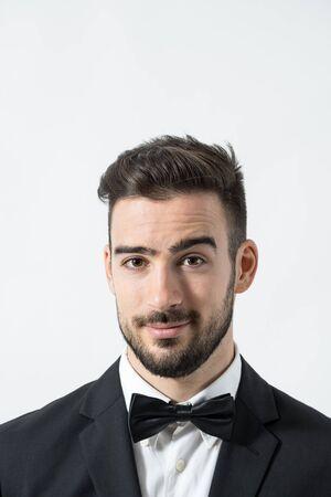 modelos hombres: Cerca de retrato de joven caballero rom�ntico con la ceja levantada mirando a la c�mara. Retrato sobre fondo gris de estudio