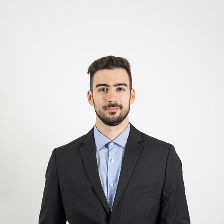 modelos hombres: La cabeza y la parte delantera del hombro retrato de hombre joven con traje y camisa azul mirando a la c�mara. Retrato sobre fondo gris de estudio Foto de archivo