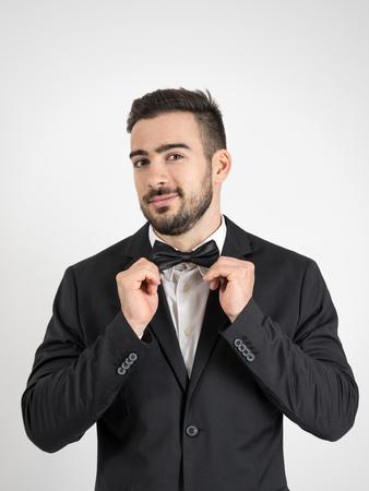 Divertido novio emocionados ajustándose la corbata de lazo que mira la cámara. Retrato desaturado sobre fondo gris del estudio con la ilustración retro.