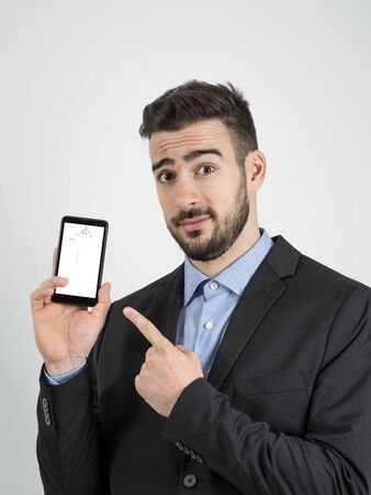 showing: Young bearded sad businessman pointing finger at broken smartphone screen. Portrait over gray studio background. Stock Photo