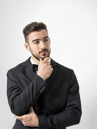 Thinking young bearded man in tuxedo with bow tie touching beard looking away. Desaturated portrait over gray studio background with retro vignette. Stock Photo