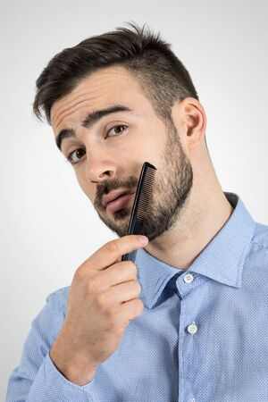 mustache: Close up portrait of young bearded man combing his beard looking at camera.  Desaturated portrait over gray studio background with retro vignette. Stock Photo