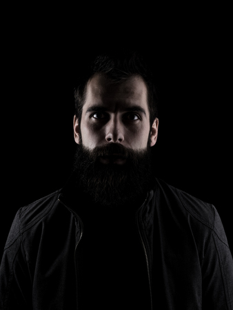 male face: Scary bearded man staring at camera. Low key dark shadow portrait isolated over black background. Stock Photo