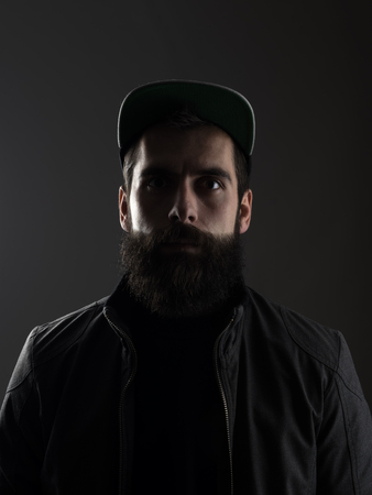 black shadow: Serious unconventional bearded man wearing baseball cap staring at camera.  Low key dark shadow portrait over black background.