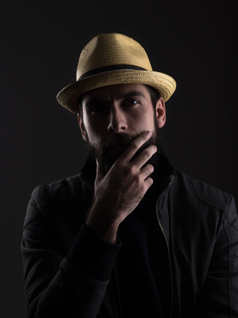 cowboy beard: Thinking bearded man wearing straw hat touching beard looking at camera. Low key dark shadow portrait over black background.